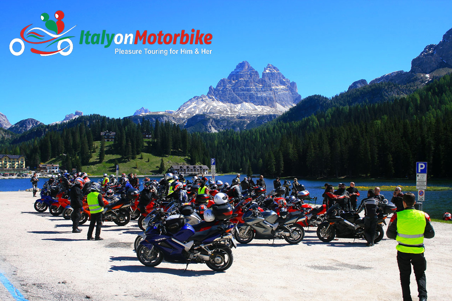 A group of bikers in the Dolomites, taking a break by a lake on our motorcycle tour of the Dolomites in the Alps