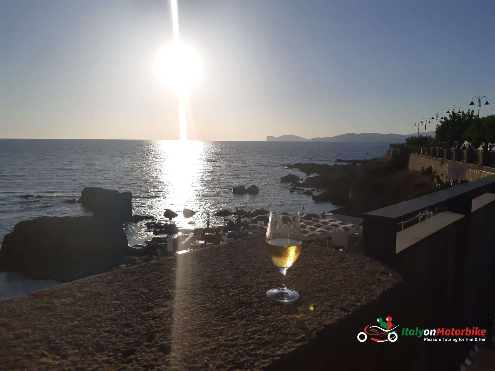 A beautiful sunset taken with a glass of white wine to end perfectly our motorcycle tour in Italy