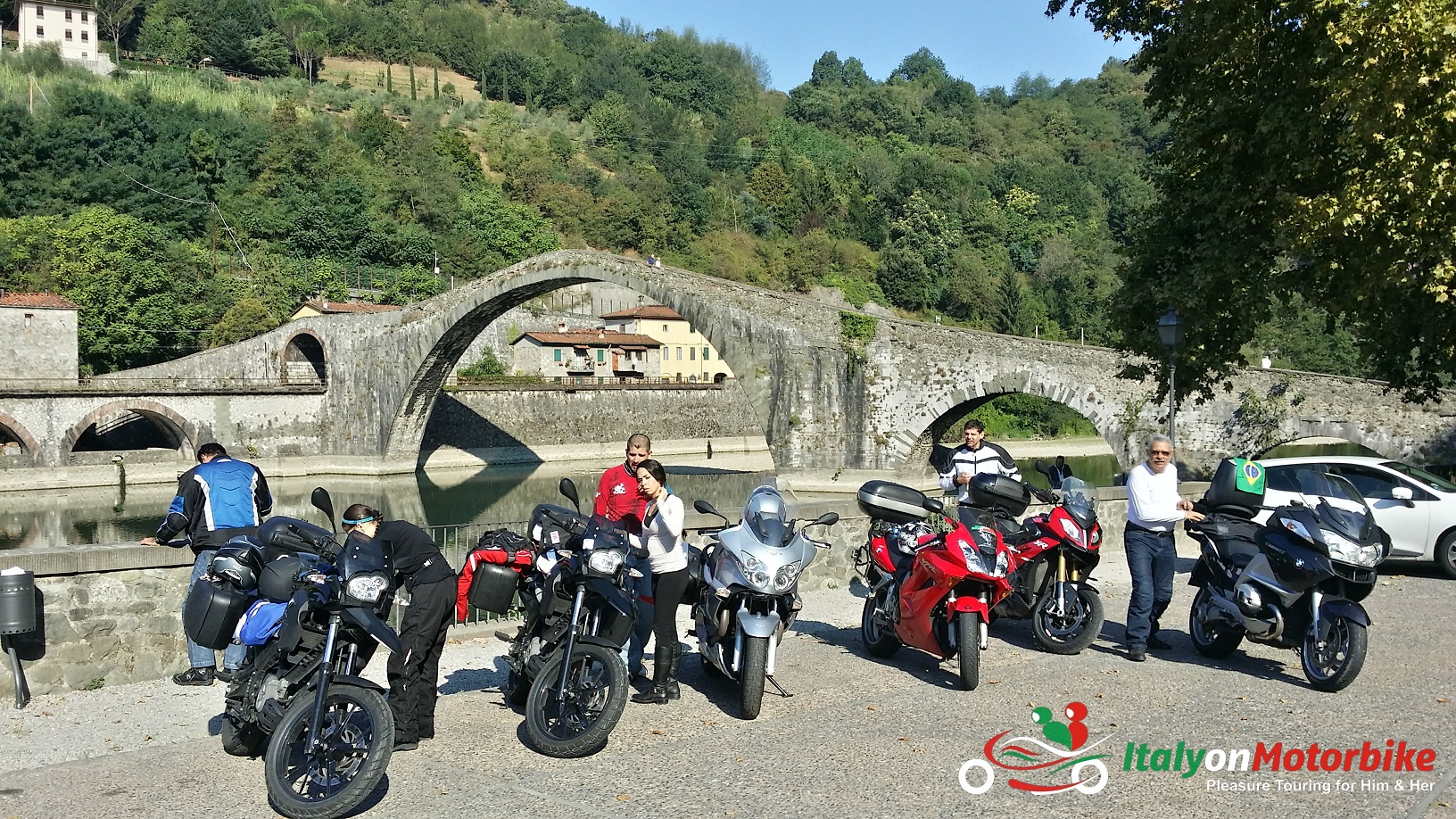 Motorcycles in front of the humpback bridge in Borgo a Mozzano on our top class motorcycle tour of Italy and a MotoGP